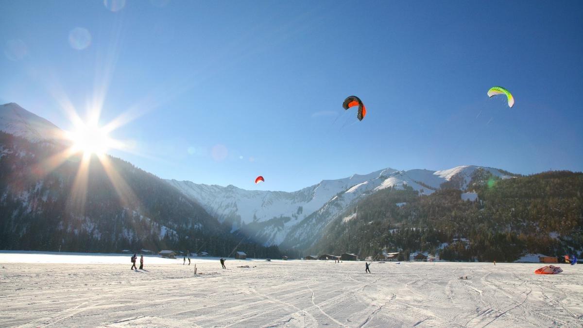 Sobald Wind aufkommt, ist der Himmel am Nordufer des Achensees bunt getupft mit Snowkites. Das Gute am trendigen Sport: Grundbegriffe erlernt jeder mittelmäßige Skifahrer oder Snowboarder binnen kürzester Zeit., © Achensee Tourismus